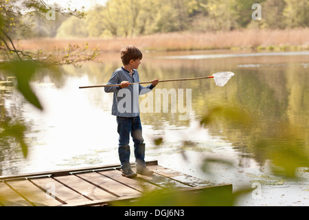 Boy standing on pier and fishing in river - Stock Photo