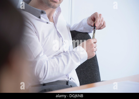 Man holding pen in business meeting, close up - Stock Photo