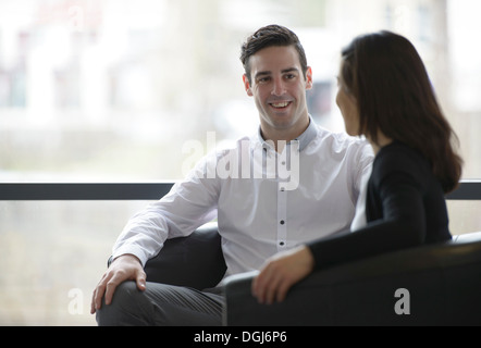 Colleagues conducting business meeting in front of window - Stock Photo