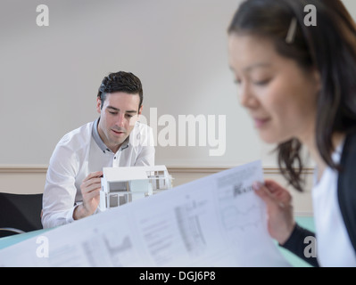 Architects inspecting model of building and plans in office - Stock Photo