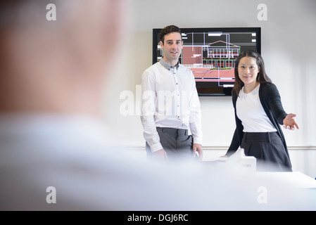 Architects making presentation in boardroom with model building Stock Photo