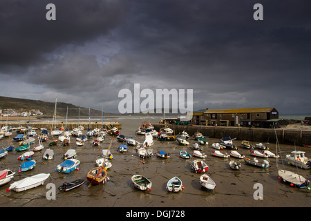 Lyme Regis harbour at low tide on a stormy day. - Stock Photo