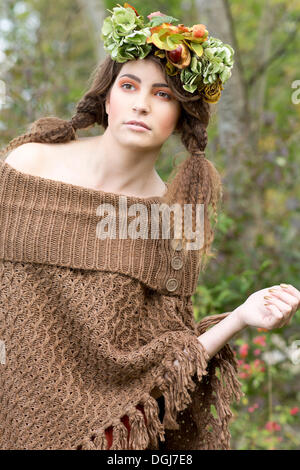 Young woman wearing a brown poncho with a flowal wreath in her hair, outdoors - Stock Photo