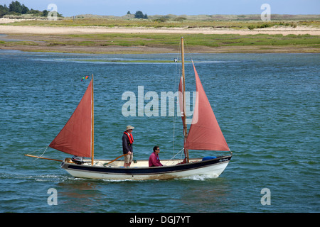 Two men sailing a boat down the channel between the harbour and beach at Wells Next The Sea. - Stock Photo