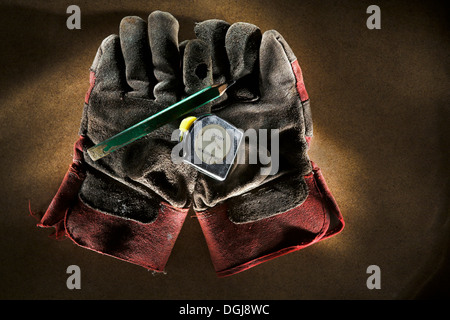 Tape measure and pencil with well worn leather work gloves. - Stock Photo