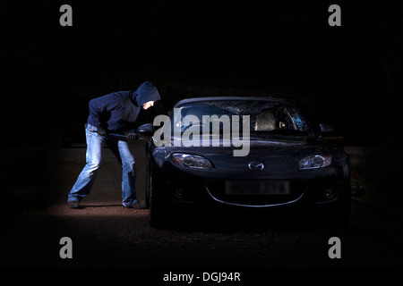 A man breaking into a parked car at night. - Stock Photo