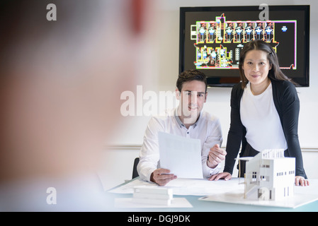 Architects making presentation in boardroom with model building - Stock Photo