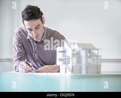 Architect working next to model building - Stock Photo