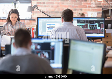 Architects working on monitors in modern office - Stock Photo