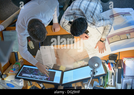 Architects working together on plans and screens at desk - Stock Photo
