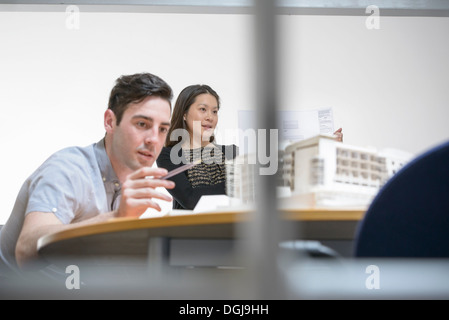 Architects making presentation in boardroom with scale model - Stock Photo