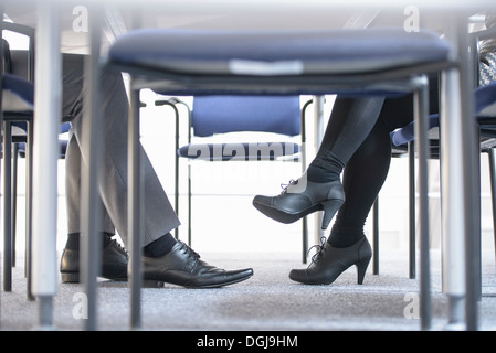 Businessman and woman in meeting, low section - Stock Photo