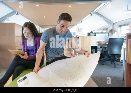 Business colleagues looking at plans in modern office - Stock Photo