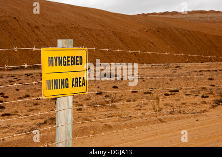 Warning sign on a barbed wire fence, mining area at the De Beers diamond mining site of the diamond coast between - Stock Photo