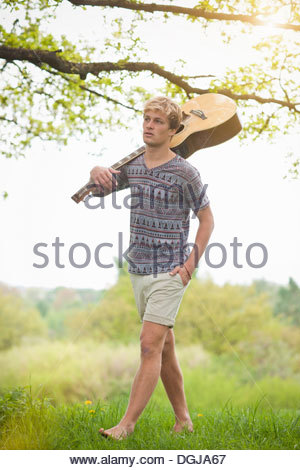 Young man walking through field with guitar - Stock Photo