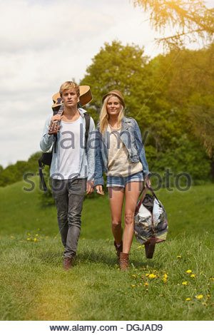Young couple walking through field with guitar - Stock Photo