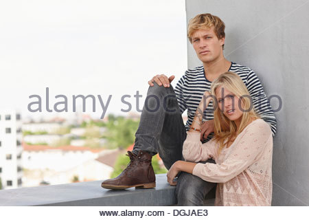Young couple on apartment balcony - Stock Photo