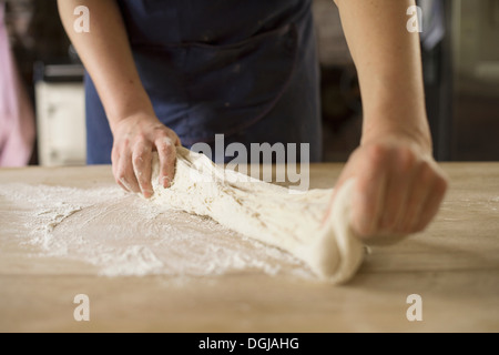 Close up of hands stretching bread dough - Stock Photo