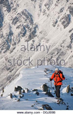Female climber walking up snow covered ridge - Stock Photo