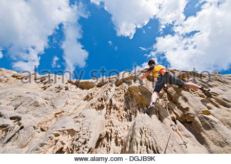 Female rock climber nearing cliff top - Stock Photo