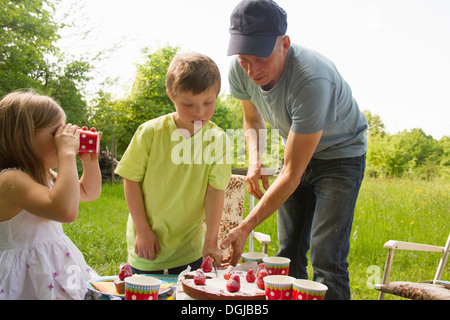 Father with two children cutting birthday cake outdoors - Stock Photo