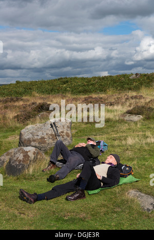 Two men lying down asleep/ resting on the ground in the Derbyshire countryside England - Stock Photo