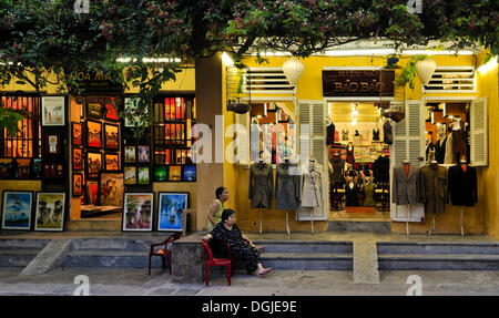 Street scene, two women in front of a tailor shop, Hoi An, Vietnam, Southeast Asia - Stock Photo