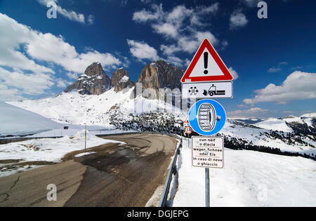 Traffic sign, warning, winter services, snow chains are mandatory in snow, in the back the Sassolungo group, Sella - Stock Photo