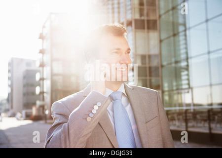 Mature businessman on cellphone in city - Stock Photo