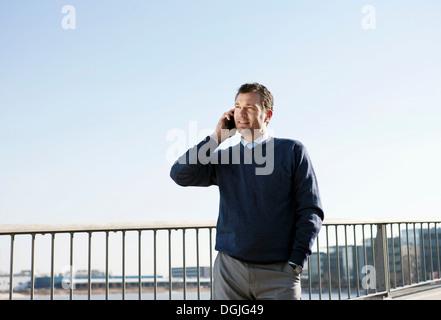 Mature man using cellphone outdoors - Stock Photo