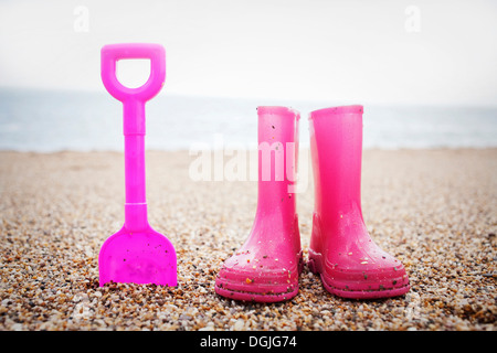 Pink spade and wellington books standing on beach - Stock Photo