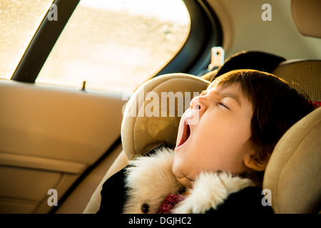 Young girl with eyes closed yawning in car - Stock Photo