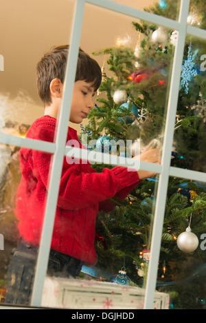 Boy decorating christmas tree in front of window - Stock Photo