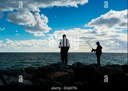 Anglers fishing off rocks at Cottesloe Beach in Perth in Western Australia. - Stock Photo
