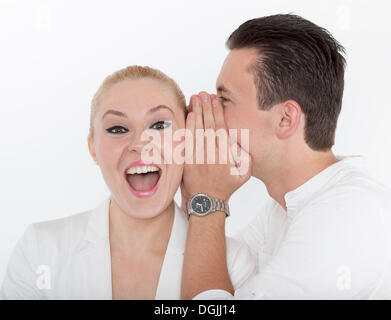 Young man whispering something into the ear of his young partner, which she receives joyfully, symbolic image for - Stock Photo