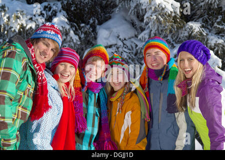 Group of young people in front of a snow-covered spruce forest, Salzburger Land, Flachau, Tyrol, Austria - Stock Photo