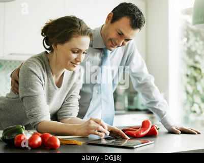 Businessman and wife using digital tablet in kitchen - Stock Photo