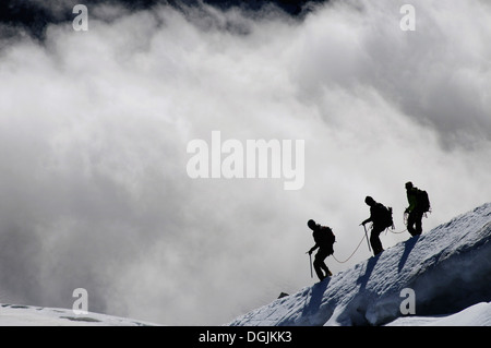 Three climbers in the alps - Stock Photo