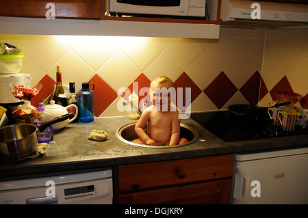 A smiling baby being bathed in the kitchen sink - Stock Photo