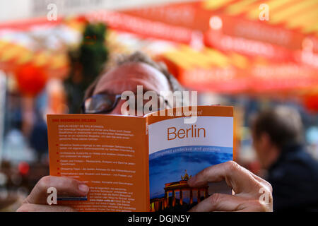Man concentrating while reading a Berlin guide while sitting at a sidewalk cafe, Berlin - Stock Photo