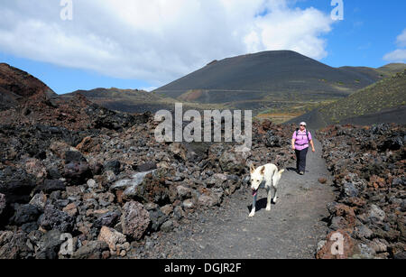 Woman walking with a dog on La Palma, in front of San Antonio Volcano, Canary Islands, Spain, Europe, PublicGround - Stock Photo