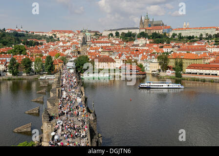 View from the Old Town Bridge Tower looking towards the Vltava river, Charles Bridge with tourists, Hradschin castle - Stock Photo