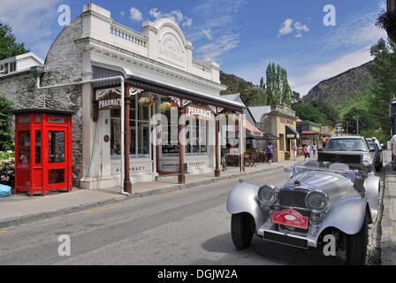 Historic buildings, pharmacy, Jaguar vintage car, gold rush town Arrowtown, South Island, New Zealand - Stock Photo