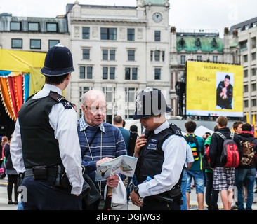Two Metropolitan Police officers helping a tourist. - Stock Photo