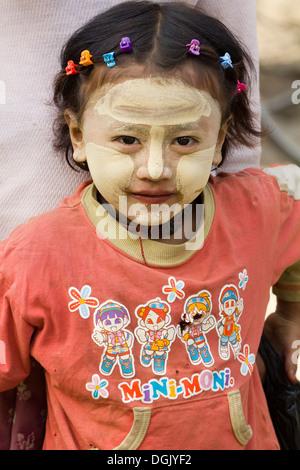 Little girl with thanaka makeup in Nyaung oo market in Bagan in Myanmar. - Stock Photo