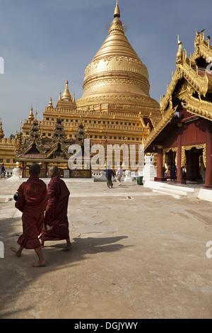 Two monks walking at the Shwezigon Pagoda in Bagan in Myanmar. - Stock Photo