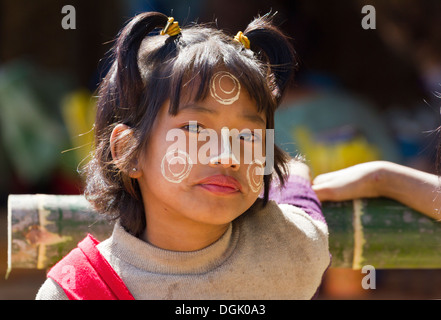 A cheeky little girl with Thanaka face decorations in Inn Thein Village in Myanmar. - Stock Photo