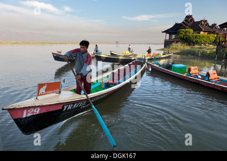 Boats moored by the Lake Inle Resort at sunset in Myanmar. - Stock Photo