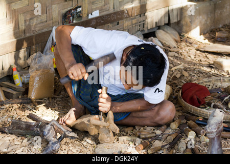 A man carving Burmese marionettes in Mandalay in Myanmar. - Stock Photo