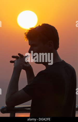 Silhouetted man on Mandalay Hill viewing point at sunset in Myanmar. - Stock Photo